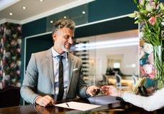 Ώριμος επιχειρηματίας στην υποδοχή ξενοδοχείων Στοκ εικόνα με δικαίωμα ελεύθερης χρήσης