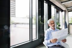 Ώριμος επιχειρηματίας στο μπλε πουκάμισο στο γραφείο Στοκ Φωτογραφίες