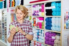 Ώριμος ευτυχής πελάτης γυναικών που επιλέγει το διάφορο νήμα στοκ φωτογραφία