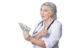 Ώριμος θηλυκός γιατρός με τα χρήματα Στοκ φωτογραφία με δικαίωμα ελεύθερης χρήσης