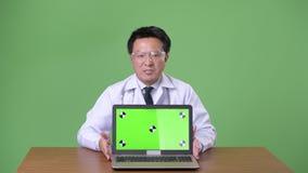 Ώριμος ιαπωνικός γιατρός ατόμων στο πράσινο κλίμα απόθεμα βίντεο