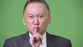 Ώριμος 0 ιαπωνικός επιχειρηματίας με το δάχτυλο στα χείλια απόθεμα βίντεο
