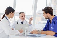 Ώριμος ιατρός παθολόγος που εξηγεί κάτι στους οικότροφους Στοκ εικόνα με δικαίωμα ελεύθερης χρήσης