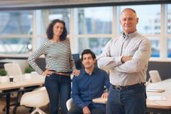 Ώριμος διευθυντής που στέκεται σε ένα γραφείο με τους συναδέλφους πίσω από τον Στοκ εικόνα με δικαίωμα ελεύθερης χρήσης