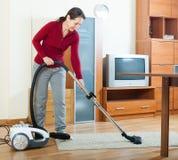 Ώριμος καθαρισμός γυναικών με την ηλεκτρική σκούπα Στοκ εικόνα με δικαίωμα ελεύθερης χρήσης
