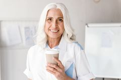 Ώριμος καφές κατανάλωσης γυναικών στο εσωτερικό στην αρχή λειτουργώντας Στοκ εικόνα με δικαίωμα ελεύθερης χρήσης