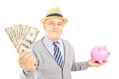 Ώριμος κύριος που κρατά μια piggy τράπεζα και τα αμερικανικά δολάρια Στοκ Εικόνες