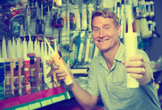 Ώριμος πελάτης ατόμων που επιλέγει το σωλήνα στεγανωτικής ουσίας στην υπεραγορά Στοκ Εικόνες