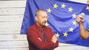 Ώριμος πολιτικός στο κοστούμι που στέκεται στη σκηνή στο φως ενάντια στις ερωτήσεις σημαιών και ganswers της ΕΕ από τους δημοσιογ φιλμ μικρού μήκους