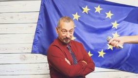 Ώριμος πολιτικός στο κοστούμι που στέκεται στη σκηνή στο φως ενάντια στις ερωτήσεις σημαιών και ganswers της ΕΕ από τους δημοσιογ απόθεμα βίντεο