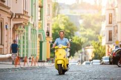 Ώριμος τύπος που οδηγά το κίτρινο μηχανικό δίκυκλο Στοκ Εικόνες