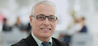 Ώριμος φιλικός άσπρος-μαλλιαρός επιχειρηματίας σε ένα σύγχρονο γραφείο Στοκ Φωτογραφία