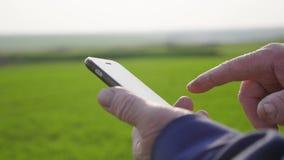 Ώριμο άτομο γεωπόνων που χρησιμοποιεί το smartphone στο αγρόκτημα γεωργίας Κλείστε επάνω τον αγρότη με το κινητό τηλέφωνο παραδίδ φιλμ μικρού μήκους