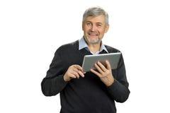 Ώριμο άτομο με την ταμπλέτα που φαίνεται ευθύ Στοκ Εικόνα