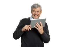 Ώριμο άτομο με την ταμπλέτα υπολογιστών που φαίνεται ευτυχές Στοκ Φωτογραφία