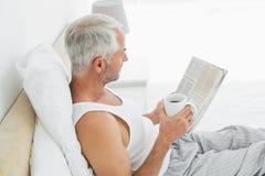 Ώριμο άτομο με το φλυτζάνι καφέ και εφημερίδα στο κρεβάτι στοκ φωτογραφία με δικαίωμα ελεύθερης χρήσης