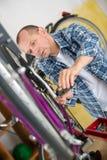 Ώριμο άτομο που επισκευάζει το ποδήλατο στο εργαστήριο Στοκ Εικόνες