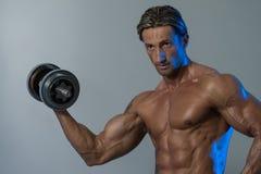 Ώριμο άτομο που επιλύει τους δικέφαλους μυς στο γκρίζο υπόβαθρο Στοκ φωτογραφία με δικαίωμα ελεύθερης χρήσης
