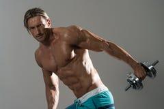 Ώριμο άτομο που επιλύει Triceps στο γκρίζο υπόβαθρο Στοκ Φωτογραφίες