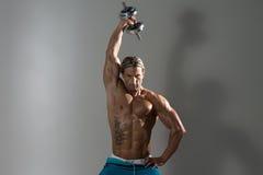 Ώριμο άτομο που επιλύει Triceps στο γκρίζο υπόβαθρο Στοκ Εικόνες