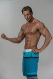 Ώριμο άτομο που κάνει την άσκηση για τους δικέφαλους μυς στο γκρίζο υπόβαθρο Στοκ εικόνα με δικαίωμα ελεύθερης χρήσης