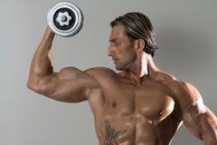 Ώριμο άτομο που κάνει την άσκηση για τους δικέφαλους μυς στο γκρίζο υπόβαθρο Στοκ Εικόνα