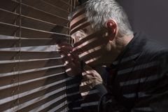 Ώριμο άτομο που κοιτάζει από ένα παράθυρο με τους τυφλούς που πετούν τις σκιές Στοκ Εικόνα