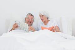 Ώριμο άτομο που παρουσιάζει εφημερίδα του στη σύζυγό του Στοκ φωτογραφίες με δικαίωμα ελεύθερης χρήσης