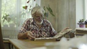 Ώριμο άτομο που φαίνεται οι παλαιές φωτογραφίες του από τη νεολαία απόθεμα βίντεο