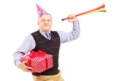 Ώριμο άτομο που φορά ένα καπέλο Κομμάτων και που κρατά ένα δώρο και ένα κέρατο στοκ φωτογραφία με δικαίωμα ελεύθερης χρήσης