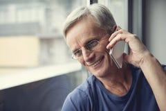 Ώριμο άτομο που χρησιμοποιεί το τηλέφωνο με τη χαρά Στοκ εικόνες με δικαίωμα ελεύθερης χρήσης
