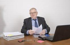 Ώριμο άτομο στην εργασία που εξετάζει τη γραφική εργασία Στοκ Εικόνα