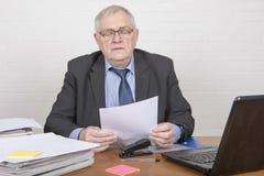 Ώριμο άτομο στην εργασία που εξετάζει τη γραφική εργασία Στοκ φωτογραφία με δικαίωμα ελεύθερης χρήσης