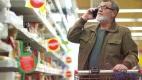Ώριμο άτομο στη γαλακτοκομική υπεραγορά τμημάτων Η ομιλία συνταξιούχων στο τηλέφωνο και επιλέγει το τυρί στα ράφια απόθεμα βίντεο