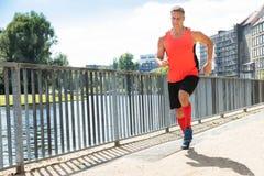Ώριμο αθλητικό άτομο που τρέχει στο πεζοδρόμιο στοκ φωτογραφία