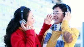 Ώριμο ασιατικό ζεύγος που ακούει τη μουσική με τα ακουστικά φιλμ μικρού μήκους
