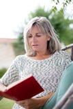 Ώριμο βιβλίο ανάγνωσης γυναικών στον κήπο στοκ φωτογραφία με δικαίωμα ελεύθερης χρήσης