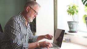 Ώριμο γενειοφόρο άτομο που εργάζεται από το σπίτι με το lap-top κάθισμα στο γραφείο κοντά στο παράθυρο απόθεμα βίντεο