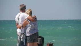 Ώριμο ζεύγος -- αγκαλιάστε την παράβλεψη της θάλασσας Το όμορφο ζεύγος των πρεσβυτέρων ποτίζει πλησίον Ευτυχείς ηλικιωμένοι που κ απόθεμα βίντεο