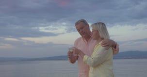 Ώριμο ζεύγος με τα γυαλιά κρασιού που περπατά θαλασσίως απόθεμα βίντεο