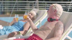 Ώριμο ζεύγος που βρίσκεται στα sunbeds κοντά στο χυμό κατανάλωσης λιμνών, ομιλία και χαμόγελο r Αναψυχή και φιλμ μικρού μήκους