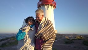 Ώριμο ζεύγος που περπατά στο ηλιοβασίλεμα στην ακτή με έναν παλαιό φάρο απόθεμα βίντεο