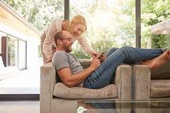 Ώριμο ζεύγος που χρησιμοποιεί στο σπίτι την ψηφιακή ταμπλέτα Στοκ Εικόνα