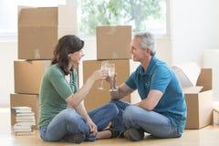 Ώριμο ζεύγος που ψήνει τα φλάουτα CHAMPAGNE στο καινούργιο σπίτι στοκ εικόνες