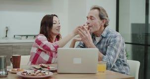 Ώριμο ζεύγος το πρωί που τρώει τα υγιή τρόφιμα και, γυναίκα που δίνει στο συνεργάτη της για να δοκιμάσει τι μαγειρεύει ενώ είναι απόθεμα βίντεο
