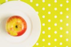 Ώριμο κόκκινος-κίτρινο μήλο σε ένα άσπρο πιάτο Κάθετη εικόνα Στοκ Εικόνες