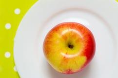 Ώριμο κόκκινος-κίτρινο μήλο σε ένα άσπρο πιάτο Στοκ εικόνα με δικαίωμα ελεύθερης χρήσης