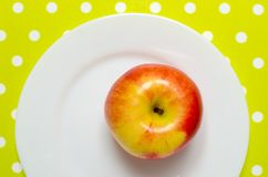 Ώριμο κόκκινος-κίτρινο μήλο σε ένα άσπρο πιάτο Στοκ φωτογραφίες με δικαίωμα ελεύθερης χρήσης
