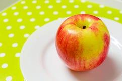 Ώριμο κόκκινος-κίτρινο μήλο σε ένα άσπρο πιάτο Στοκ εικόνες με δικαίωμα ελεύθερης χρήσης