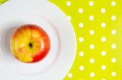 Ώριμο κόκκινος-κίτρινο μήλο σε ένα άσπρο πιάτο Στοκ φωτογραφία με δικαίωμα ελεύθερης χρήσης
